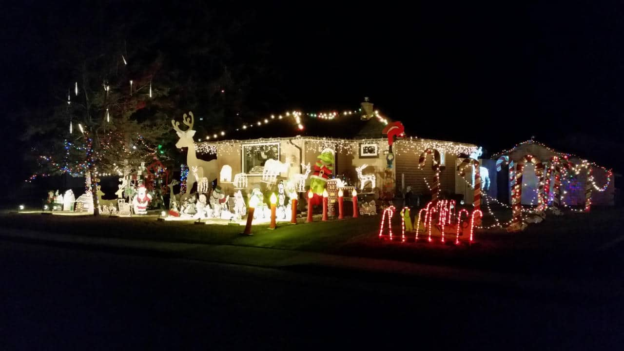Home with Christmas decorations lit up with candy canes, nativity scenes and cartoon characters